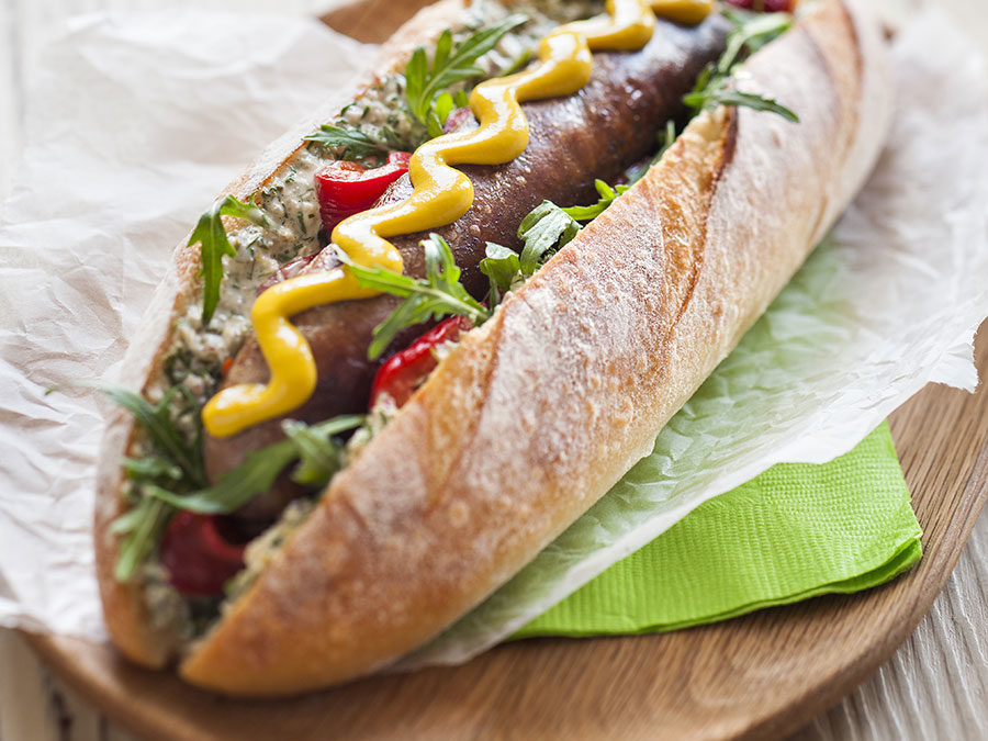 Chorizo hot dog with roasted red capsicum, salsa verde mayonnaise & rocket