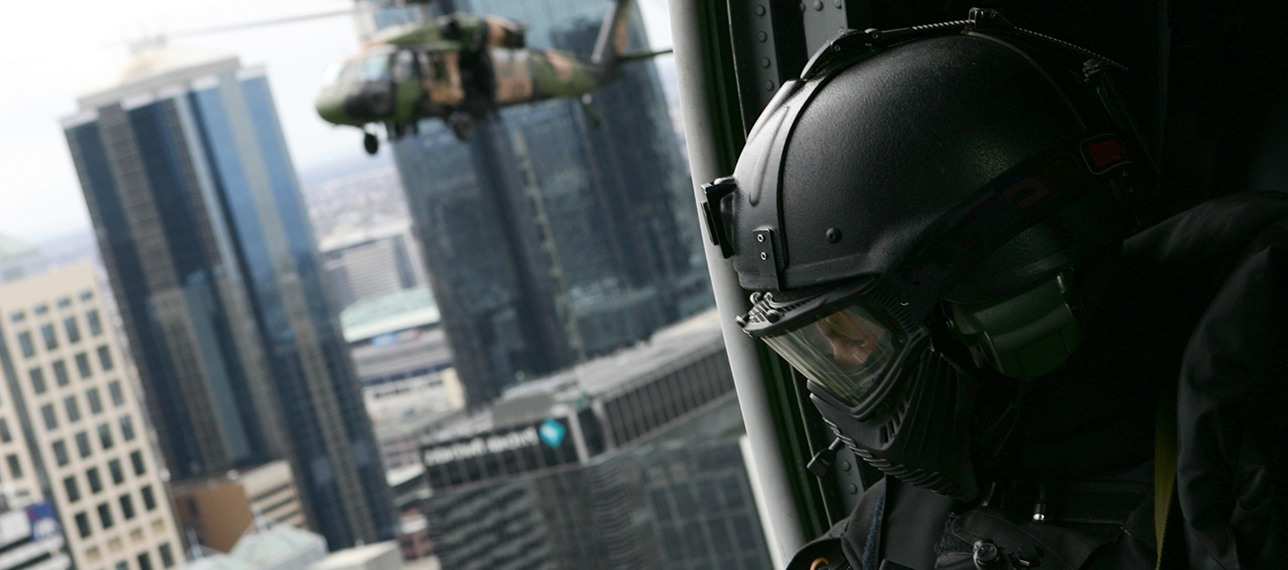 Special forces soldier in helicopter flying over cityscape