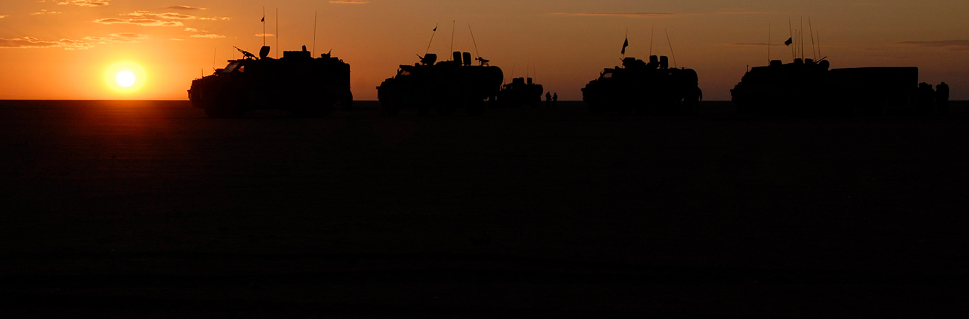 Silhouette of armored troop carriers against a setting sun