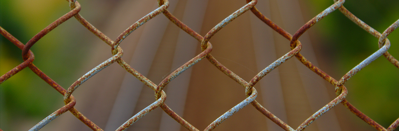 Rusty chain link fence with bokeh background