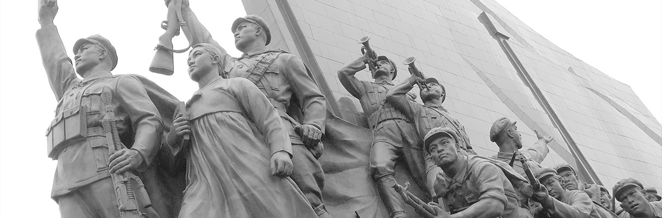 Communist style sculpture of soldiers and workers against a background of stark architecture