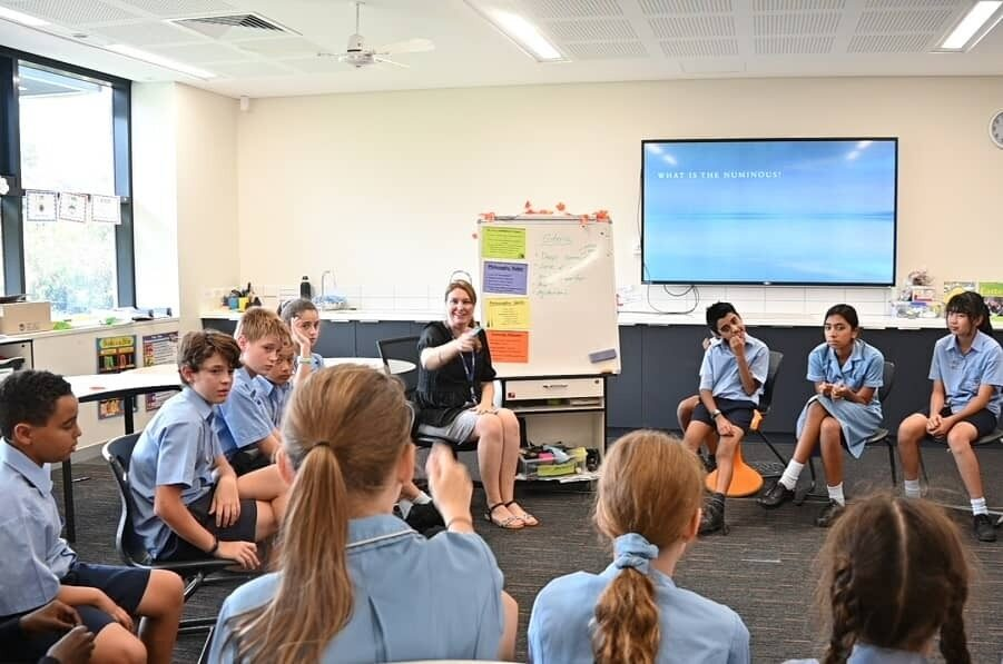 All Saints College students on chairs in a circle learning from teacher