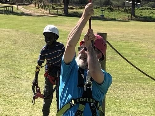 Bishop Jeremy James on flying fox with child looking on