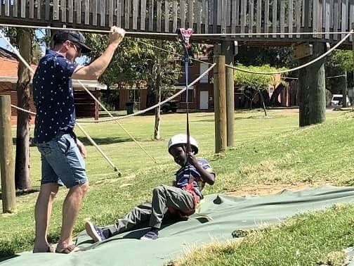 Child and adult playing on flying fox