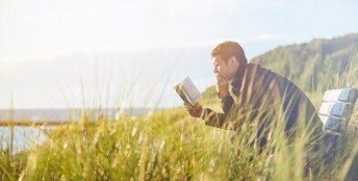 Man reading at beach sitting on bench freely thumbnail