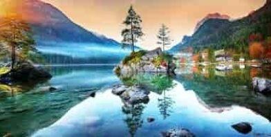 Sunrise over lake rock island mountains reflection