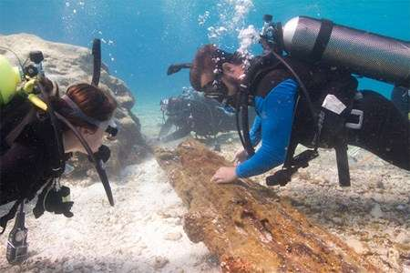 Two scuba divers inspecting a piece of timber from shipwreck