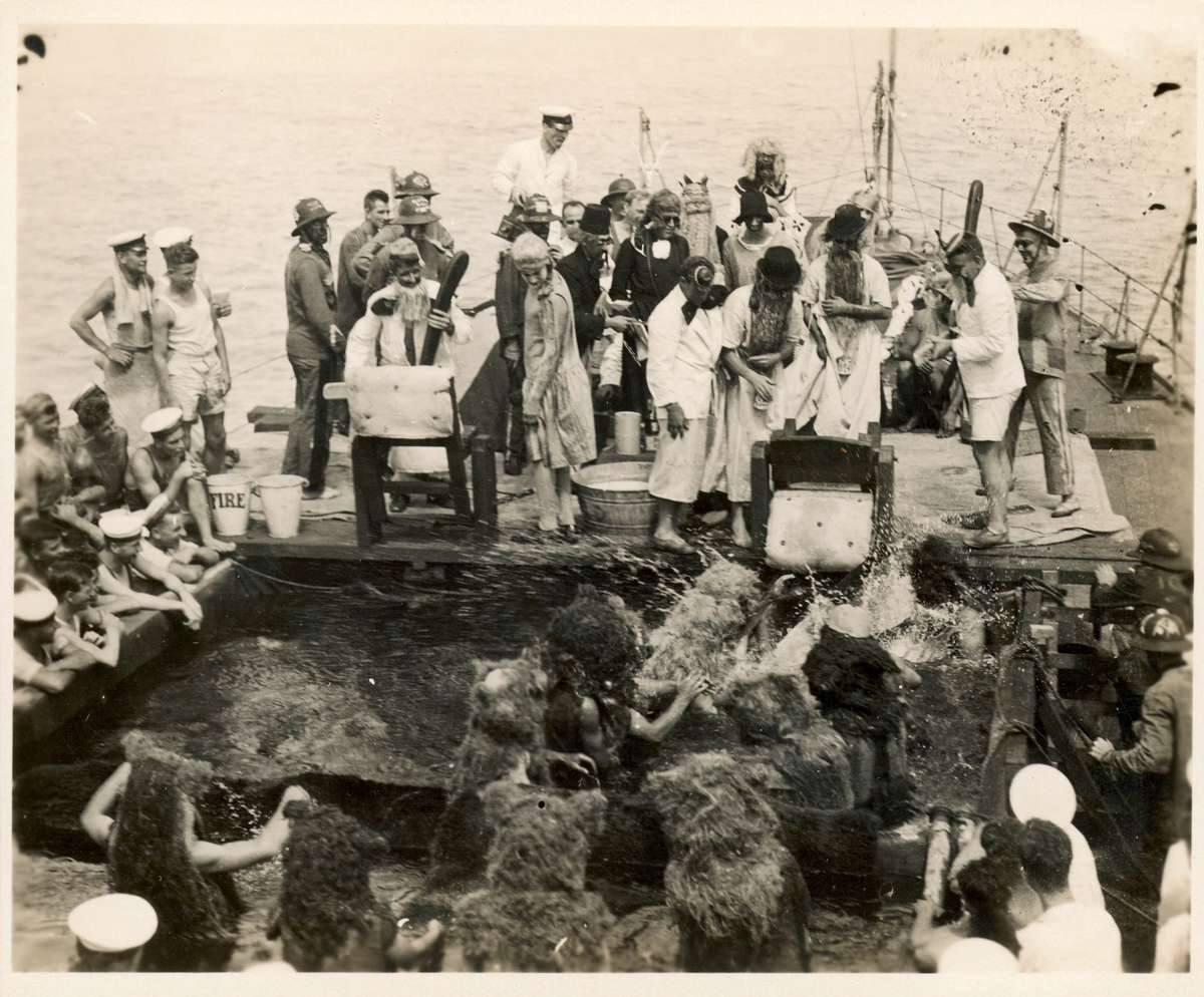 Crossing the Line Ceremony, probably onboard HMAS MELBOURNE c 1928, showing King Neptune, his court and bears dunking inductees.