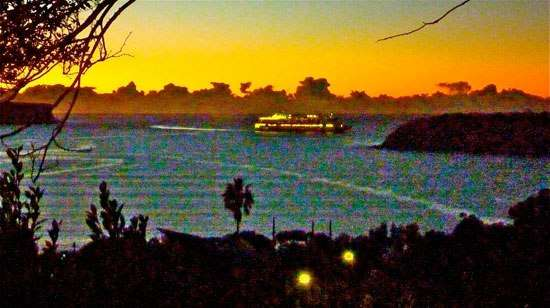 Cruise ship on Sydney Harbour at dusk, with sun setting and ship lights on