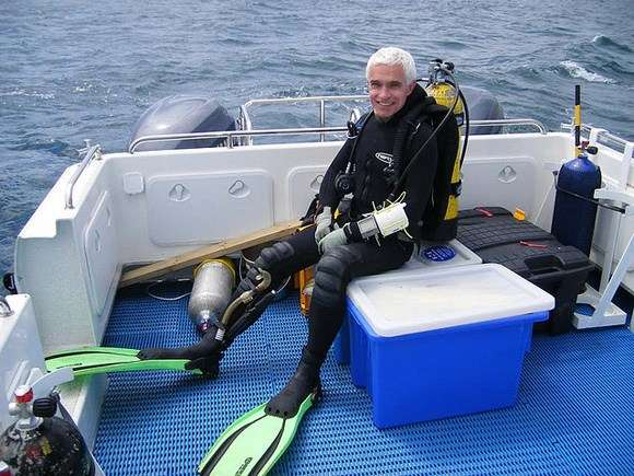 Kieran wearing scuba gear sitting on boat at sea