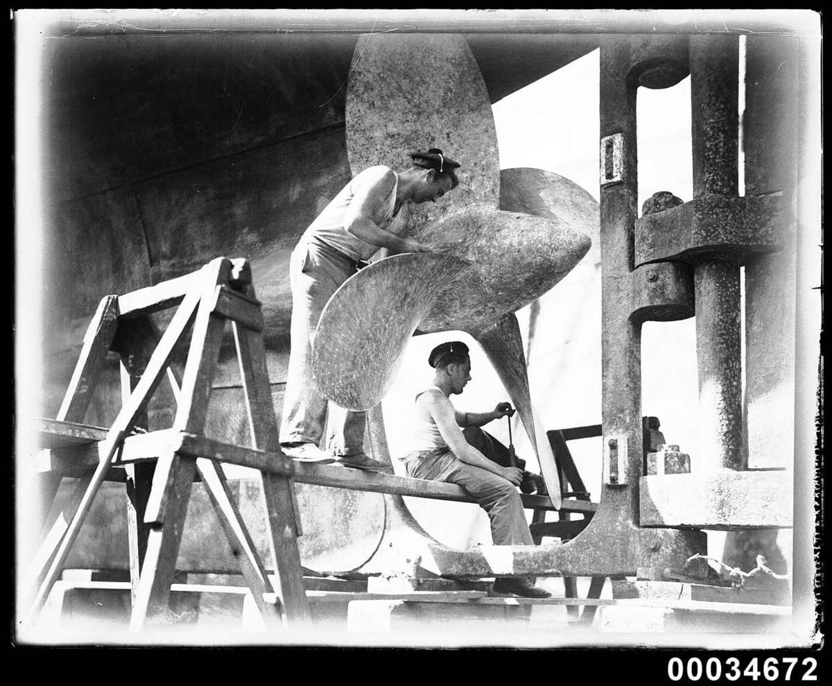 Two sailors cleaning a propeller of the French warship Bellatrix, 1930-1932 Photographer: Samuel J Hood Studio ANMM Collection