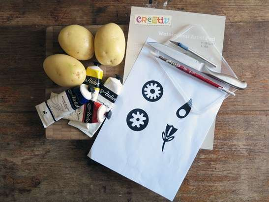 All materials laid out, potatoes, knife, craft blade, chopping board, paint, paint brush, art paper