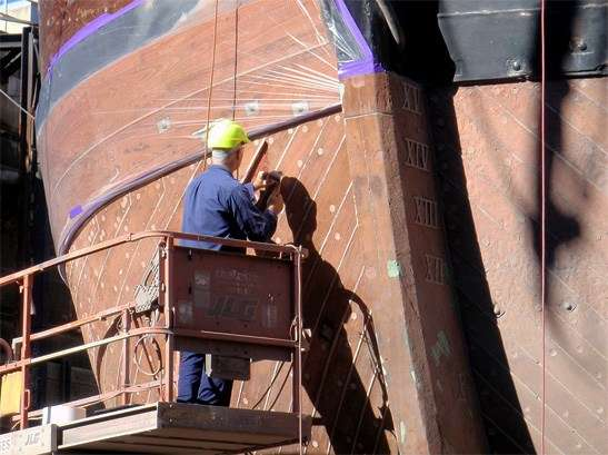 Caulking the hull of HMB Endeavour replica in recent dry-dock visit.