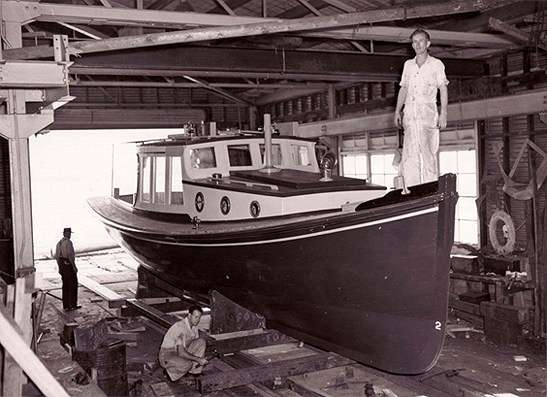 Black and white photo showing men working on a wooden boat in a boat shed