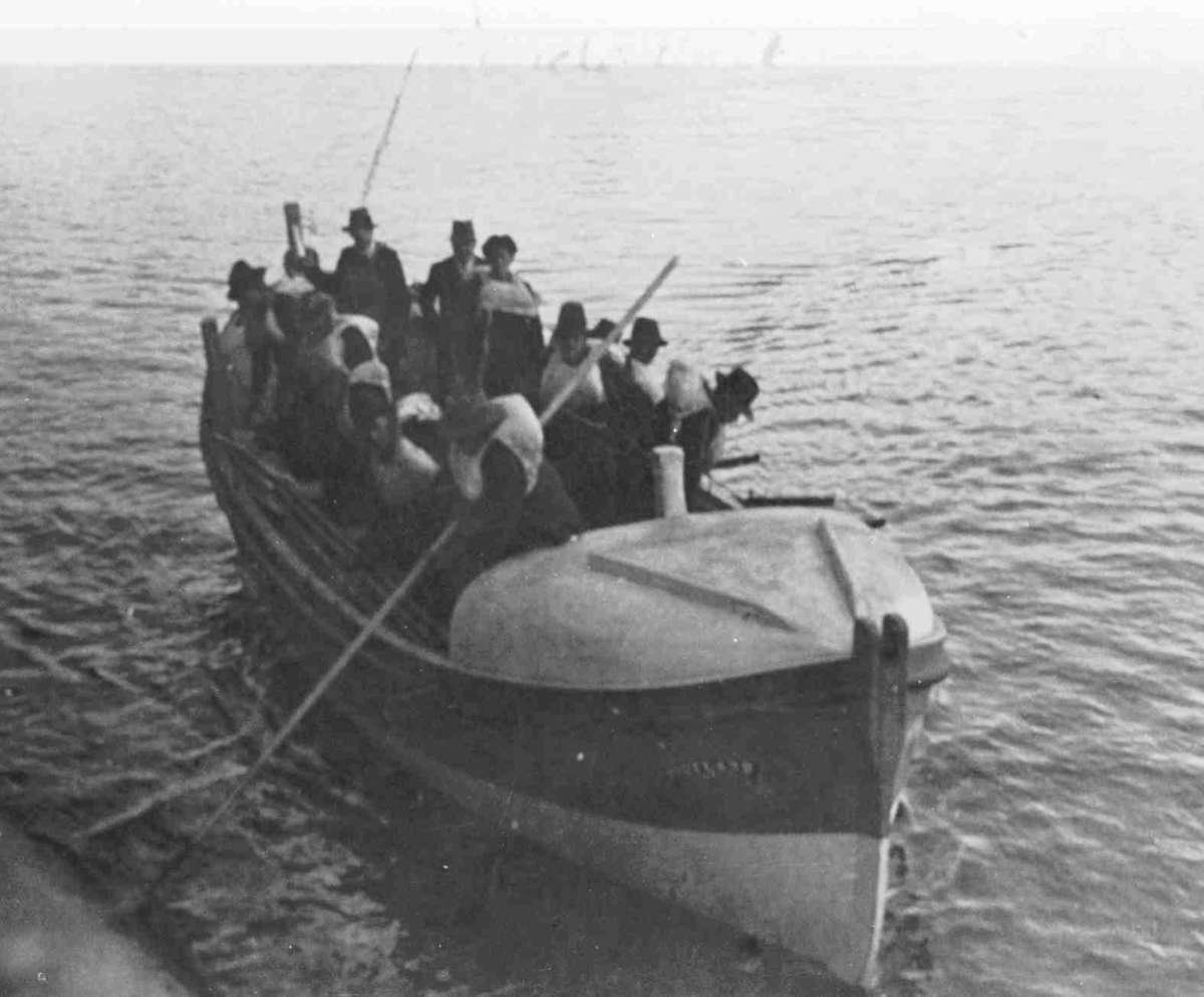 Wooden lifeboat on water full of people