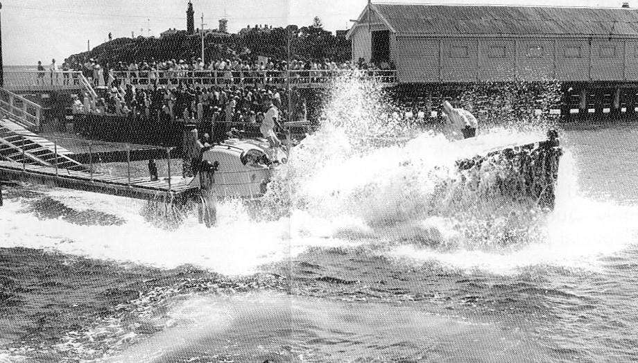Boat entering water with splash and onlooking crowd