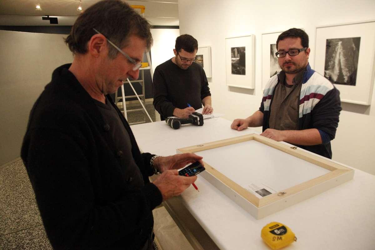 Three museum staff members installing photographs