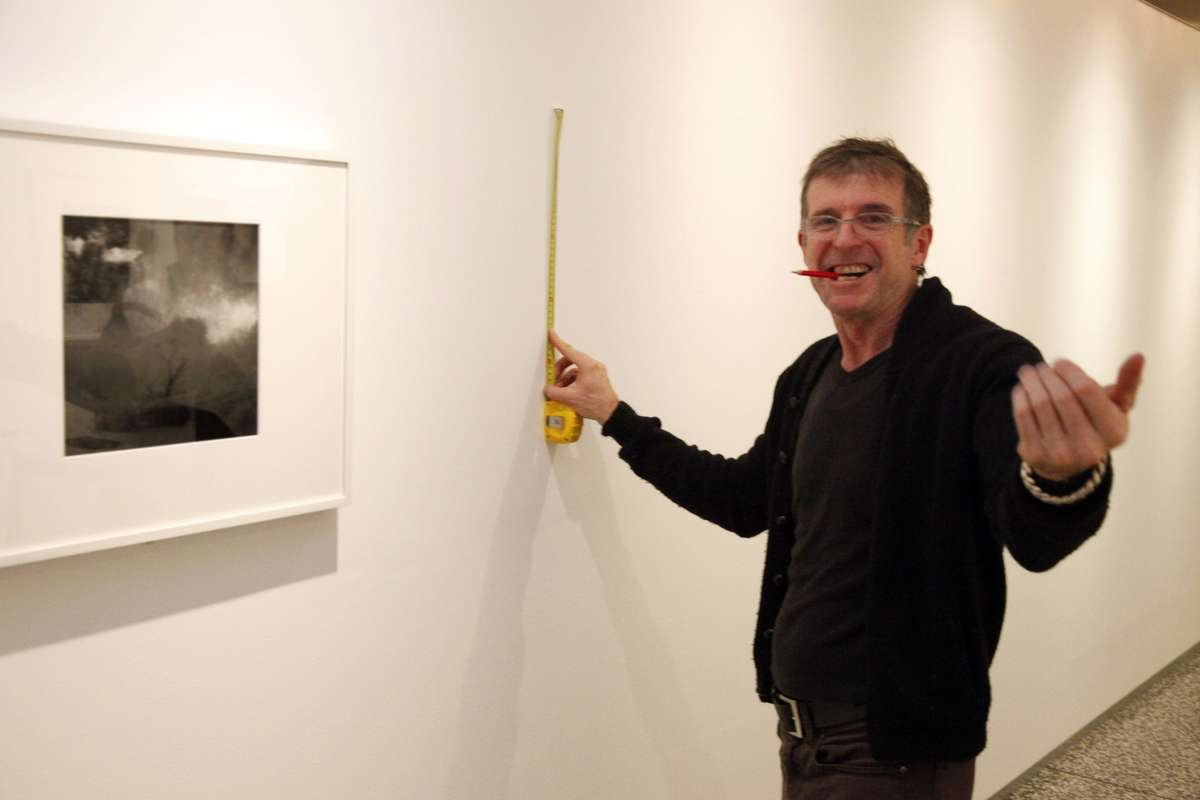 Man with tape measure next to photo on wall gesturing to the camera with open hand