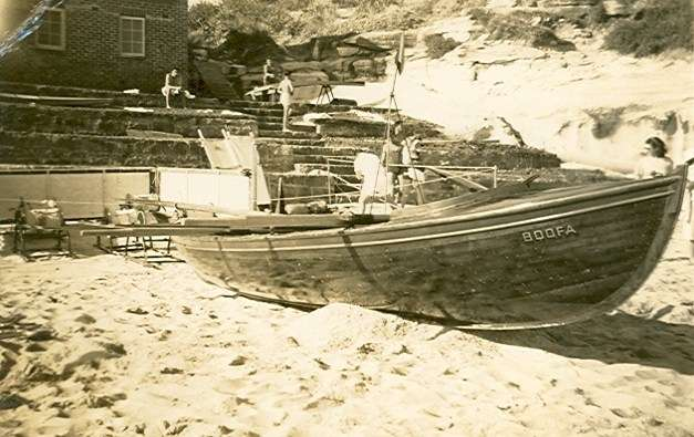 Black and white photo of wooden lifeboat on beach