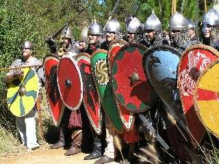 Warriors of the New Varangian Guard advance in shield wall formation