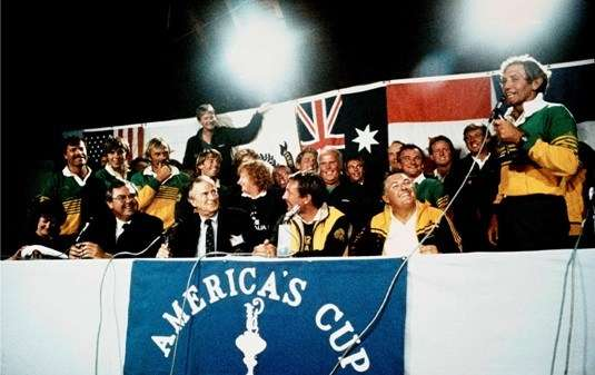 Group of Australians at a press conference desk, Australian flags in background, America