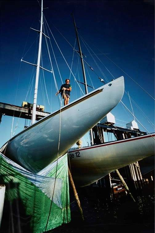 Yacht out of water with fabric covering the keel, a man stands on board the yacht