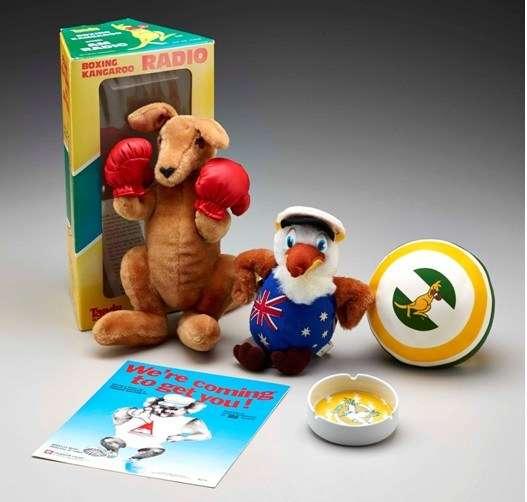 Photo of souvenirs: Plush boxing kangaroo toy, plush kookaburra toy, small ball with boxing kangaroo graphic, ashtray with yellow kookaburra graphic, poster with koala graphic and slogan