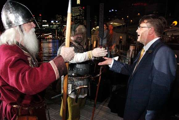 Man dressed as Vikings offers a small bag of coins to the director of the museum