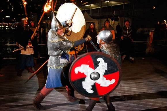 Two men dressed as Vikings fight with swords and sheilds