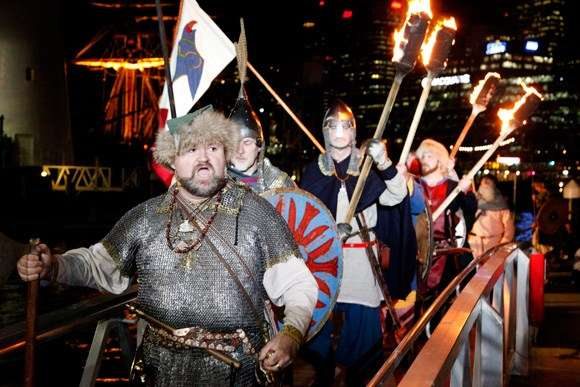 Group of people dressed as Vikings walk up ramp, holding fire torches