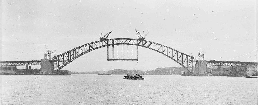 The Bridge under construction in 1930, the first piece of the deck is hung in place. Photographer Samuel J Hood. ANMM Collection