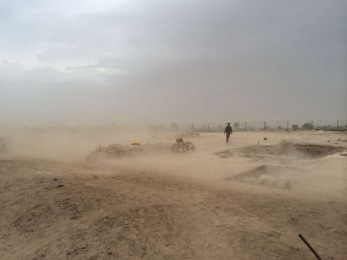 Archaeologist Dr Andrew Madden walking through a duststorm at the site of Khirbat ash-Shaykh 'Īsā. Photo: Peter Edwell 2013