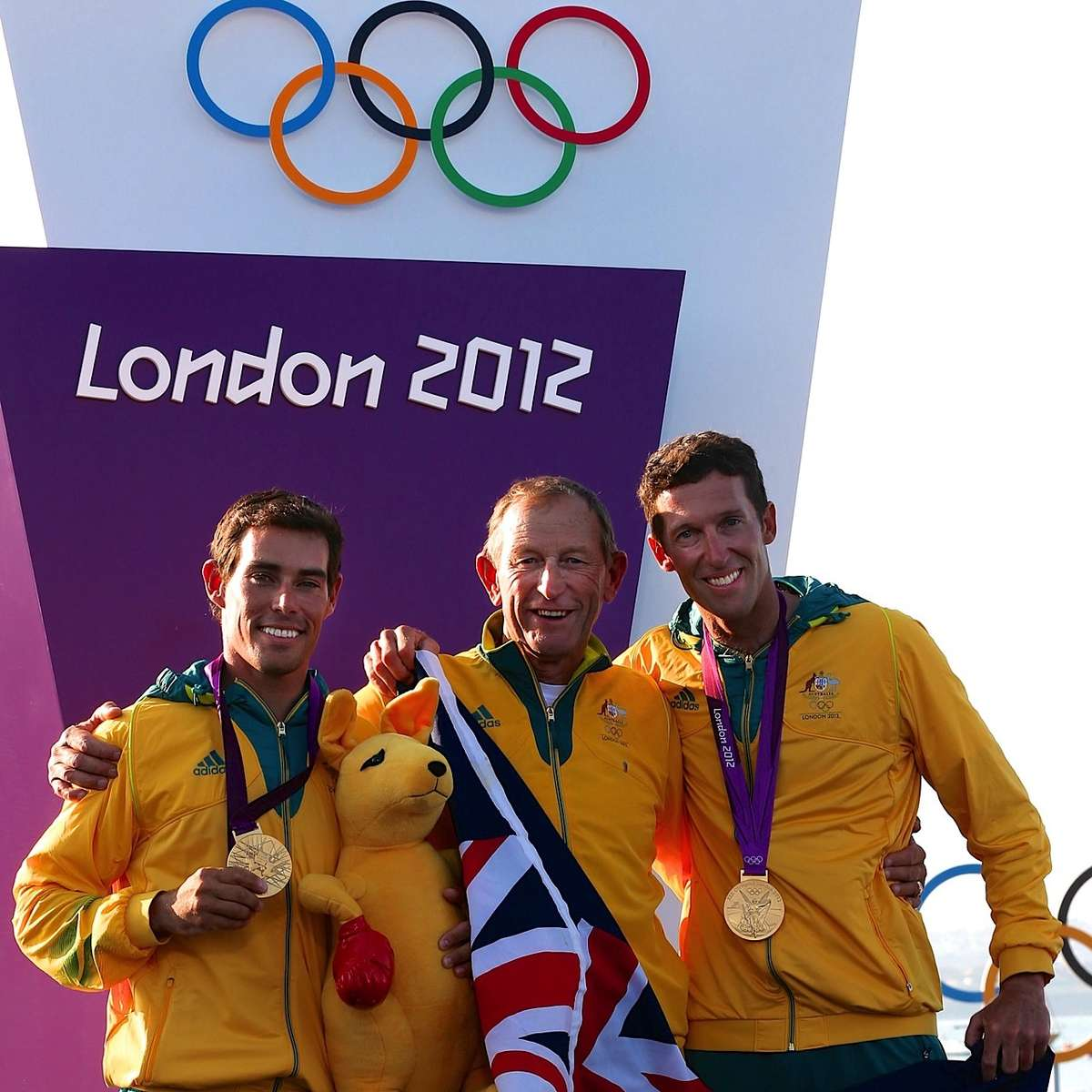 Skipper Mathew Belcher, coach Victor Kovalenko, crew Malcolm Page on the gold medal podium, London 2012 Olympic Games