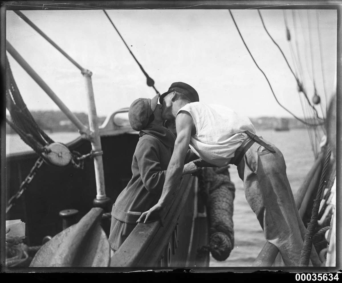 Man and woman kissing across two vessels