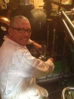 Mark Dye, 2nd engineer, steam boat owner and steam enthusiast, working on the Mumford circulating pump and in his favourite office, the engine room of a steam vessel.  Photo by Tom Lord.