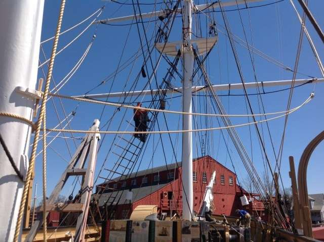 Working on the rigging of the Charles W Morgan, in the background the H.B. du Pont Preservation Shipyard.