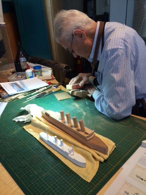 Museum volunteer model maker Col Gibson preparing waterline models for a dazzle paint scheme