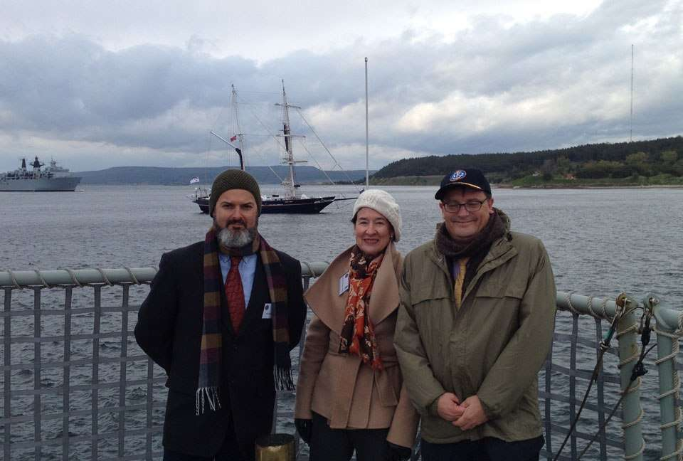 RAN Maritime Archaeology curator Dr James Hunter, ANMM Councillor the Hon. Margaret White AO, and ANMM Director Kevin Sumption rugged up for the voyage back to Çanakkale. HMS Bulwark and STS Young Endeavour are visible in the background.