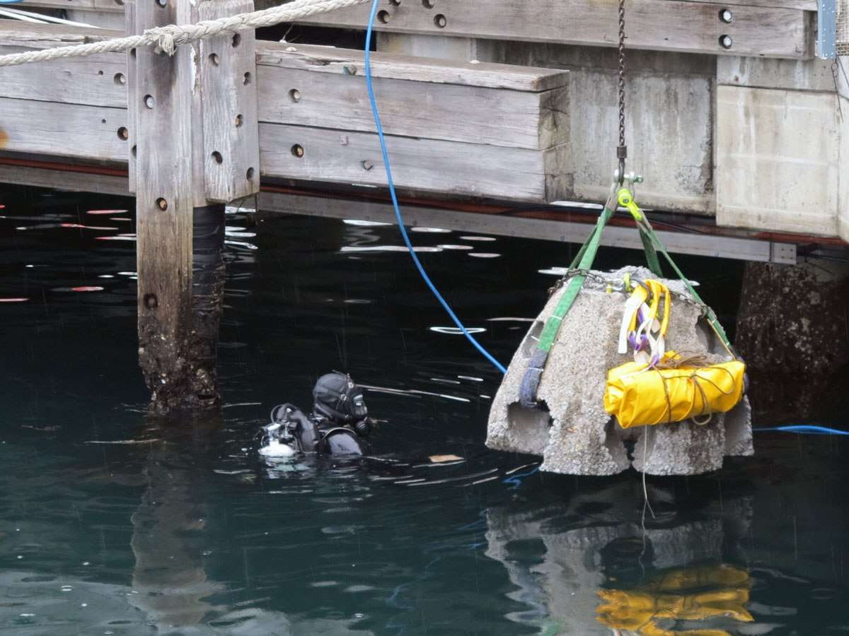 The Reef Ball, with inflatable lift bag, is lowered into the water where James and Lee wait.