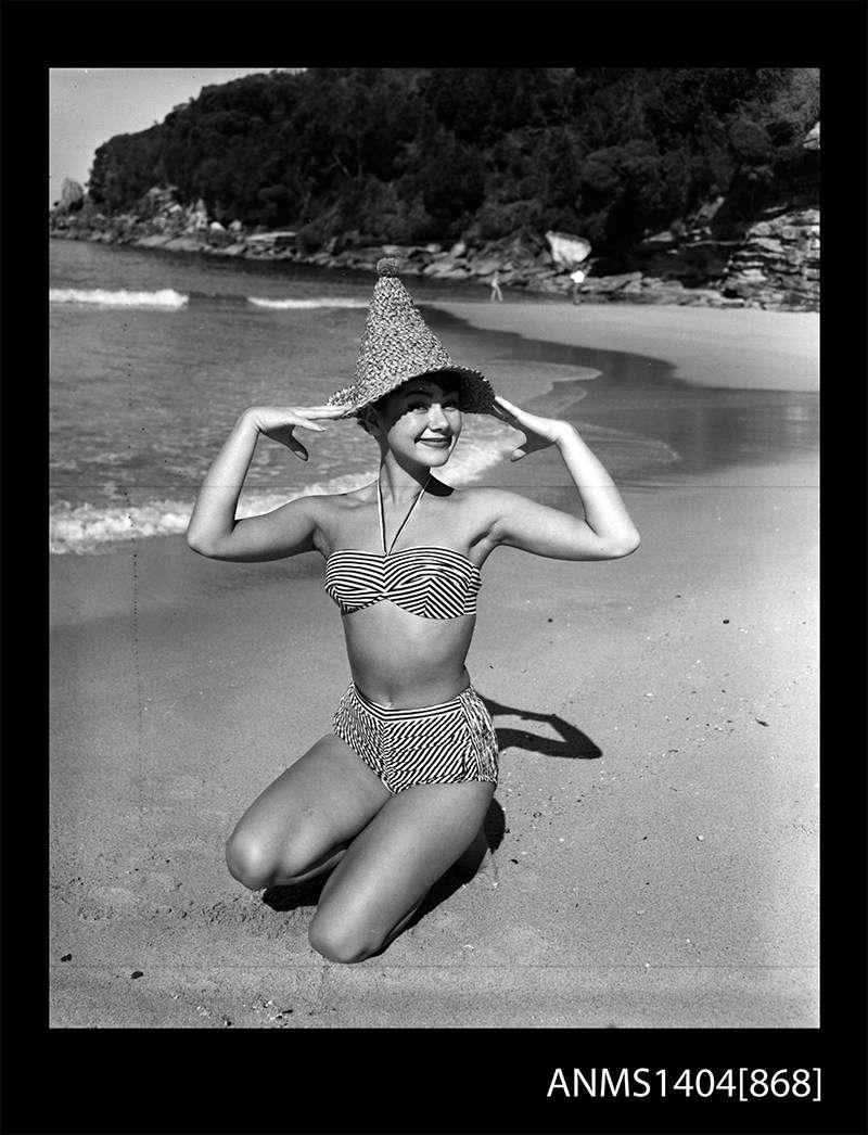 Swinsuit model posing on a beach, Gervais Purcell c 1953