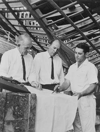 Photograph of Trevor Gowland (right) 29 year old foreman shipright, discusses plans for a new yacht with 41year old Sydney boatbuilder Trygve Halvorsen (left) and 43 year old Magnus Halvorsen