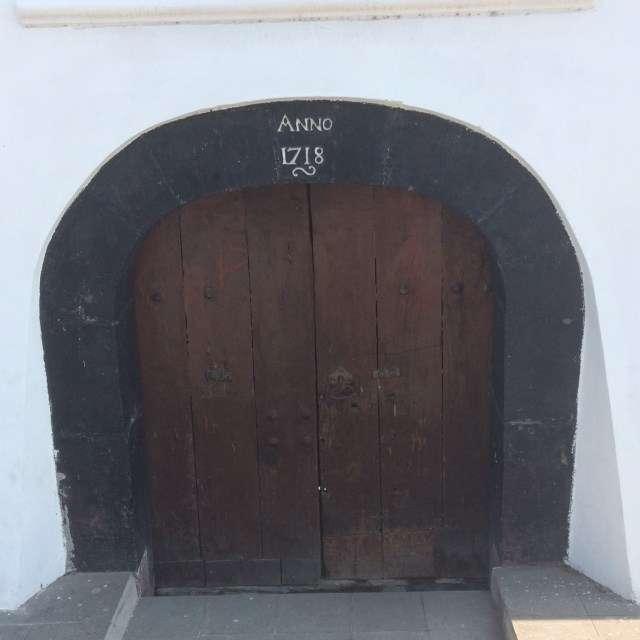 A doorway dated 1718 slightly sunken over the years