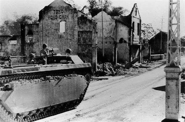 A British tank moving along the ruined streets of Surabaya, November 1945. Imperial War Museum Collection