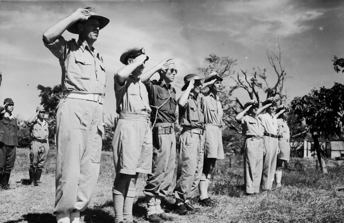 Australian and Dutch military personnel salute the Dutch flag in a transfer from Japanese military personnel (in rear) on Ceram Island, October 1946. ANMM Collection