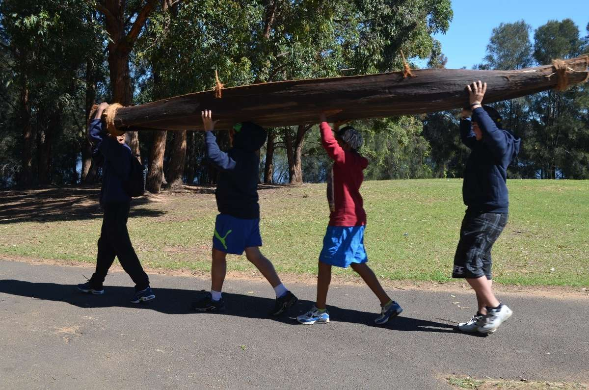 Lawrence Hargrave school students heading to launch a traditional bark canoe (nawi) they made as part of the museum's Indigenous watercraft outreach program in 2014. Photograph Donna Carstens
