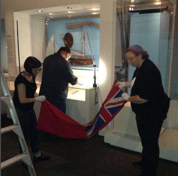 Conservation and registration staff remove the red ensign from display. Image: ANMM.