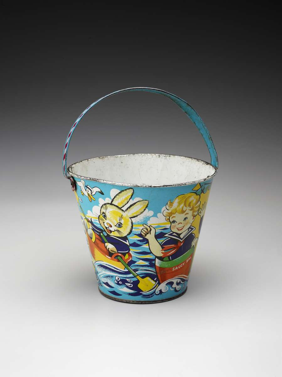 Child's toy sand bucket, manufactured by Chad Valley Toys and featuring the boat 'Saucy Sal', circa 1930. ANMM Collection 00001533.