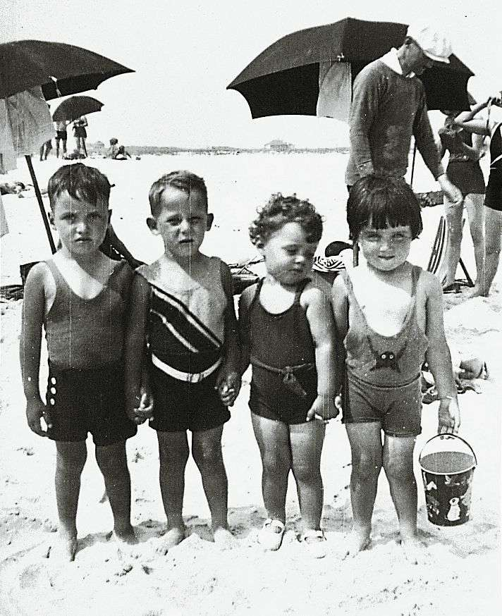Family outings - complete with toy buckets - have long been a staple of going to the beach. Image via the Vintage Everyday.