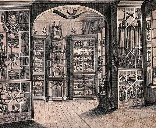 Room inside Richard Green's Museum at Litchfield, note the Pacific items in the left cabinet. (source – Wikimedia)