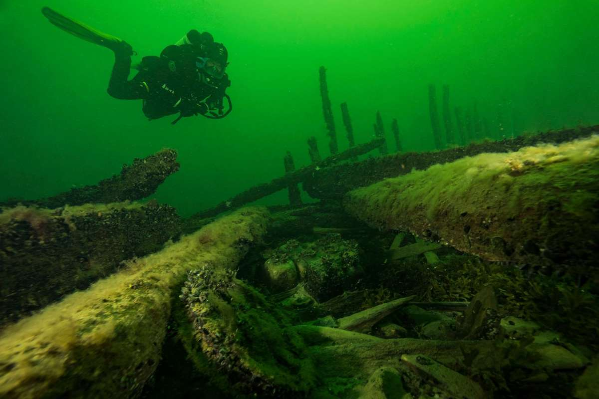 Diving on the 1660 wreck of Resande Mannen. In the foreground are a bronze sheave and a box with square medicine glass bottles, nestled between two deck beams. Photograph Jens Lindström May 2016
